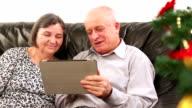 Senior couple using digital tablet at Christmas video