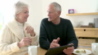 Senior Couple Using Digital Tablet At Home video