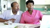 Senior Couple Using Laptop At Home Whilst Having Lunch video