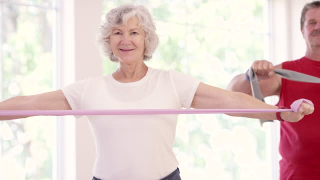 Senior Couple Using Resistance Bands during Fitness Class video