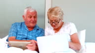 Senior couple using tablet and laptop video