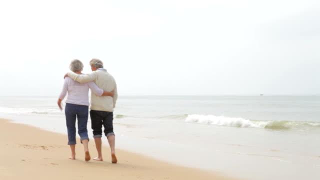 Senior Couple Walking Along Misty Beach video