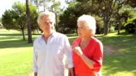 Senior Couple Walking Through Park Talking video