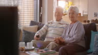 Senior couple watching a fun TV show at home video