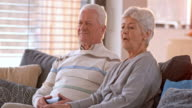 SLO MO Senior couple watching television on the sofa video