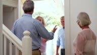 Senior Couple Welcoming Visiting Friends At Front Door video