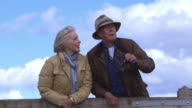 Senior Couple With Binoculars Leaning Against Wooden Gate video