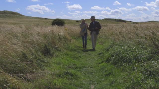 Senior Couple With Binoculars Walking In Countryside video