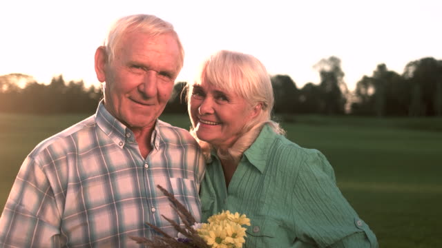 Senior couple with bouquet smiling. video