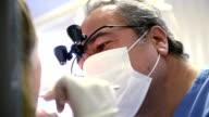 Senior dentist working video