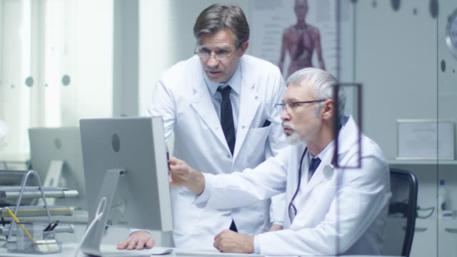 Senior Doctor and His Assistant Discuss Patient's Log on Personal Computer. In Slow Motion. video