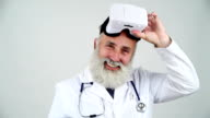 Senior doctor takes off his glasses virtual reality, happily smiling on a gray background video