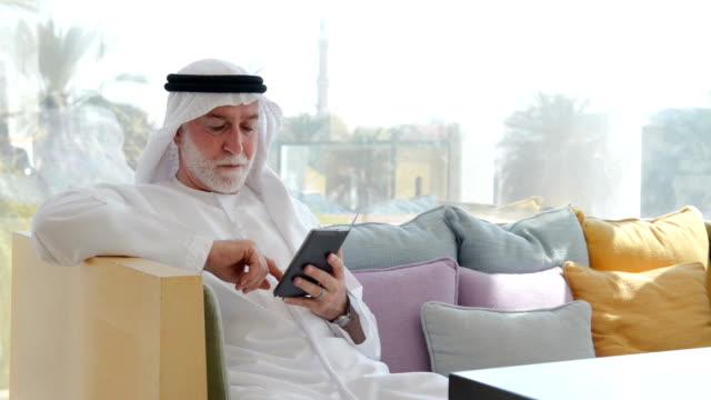 Senior Emirati man using a smartphone video