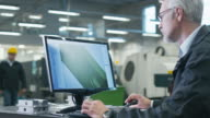Senior engineer in glasses is working on a desktop computer in a factory. video
