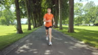 SLO MO TS Senior female jogging through tree avenue video