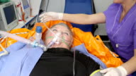 Senior female patient receiving advanced emergency medical care in ambulance video