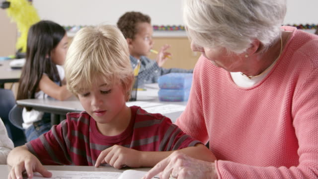 Senior female teacher helps young schoolboy reading in class video