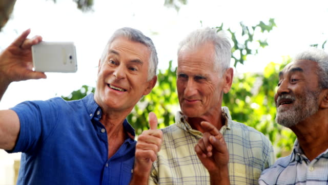 Senior friends taking selfie with mobile phone 4k video