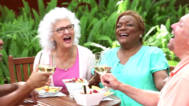 Senior friends talking, eating, drinking and laughing video