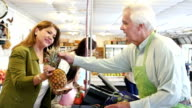 Senior grocer assists mid-adult Hispanic customer at check-out video