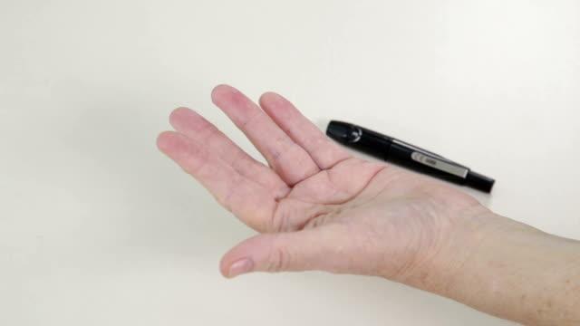 Senior hands pricking finger in insulin level test video