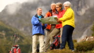 senior hikers in mountains with map video