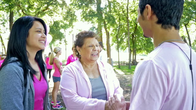 Senior Hispanic woman signing up for breast cancer awareness race with granddaughter video