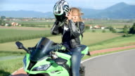 Senior lady taking off her helmet after riding a motorbike video