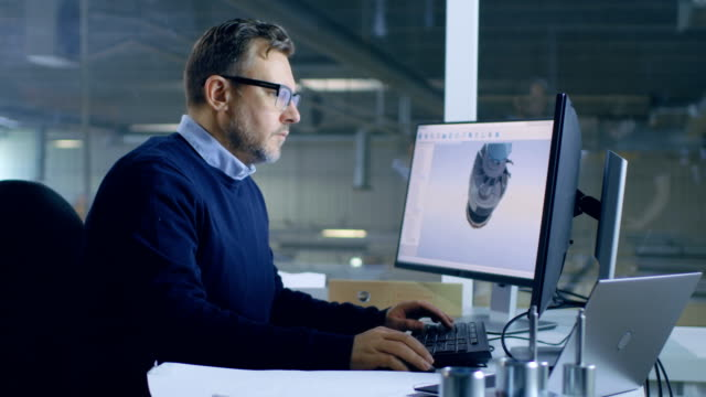 Senior Male Engineer Works on 3D Turbine/ Engine Design on His Personal Computer with Help of Cad Software. In the Background We See Big Factory. video