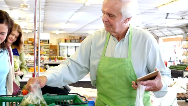 Senior male grocer is helping mother and daughter at check out at produce market video