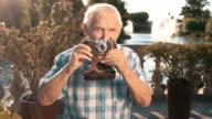 Senior male holding camera. video