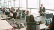 Senior male manager addressing workers in open plan office video