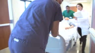 Senior Male Patient Being Wheeled Along Hospital Corridor video