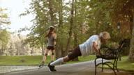 DS Senior male runner doing stretching exercises on park bench video