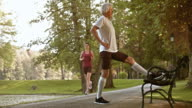 DS Senior male runner stretching on the park bench video