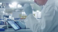 Senior male scientist is using a tablet computer in a laboratory. video