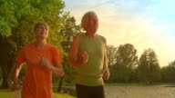 SLO MO TS Senior man and woman jogging at sunset video