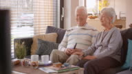 Senior man and woman watching TV and laughing video