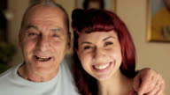 senior man and young girl smiling together. video filmed in close-up video