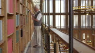 DS Senior man browsing books on s library's balcony video