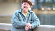 Senior man by waterfront, laughing at camera video