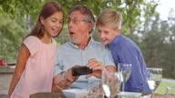 SLO MO Senior man checking photos on phone with grandkids video