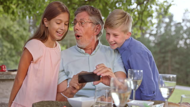 SLO MO Senior man checking photos on the phone with his grandkids video