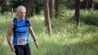 SLO MO DS Senior man competing in a trail marathon in the forest video