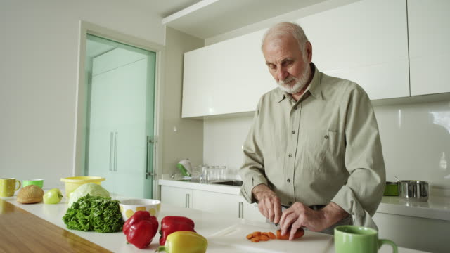 Senior man cooking a healthy meal at home video