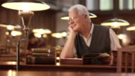 DS Senior man daydreaming in library's reading room video