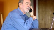 Senior Man Discusses Bills and Documents over Phone video