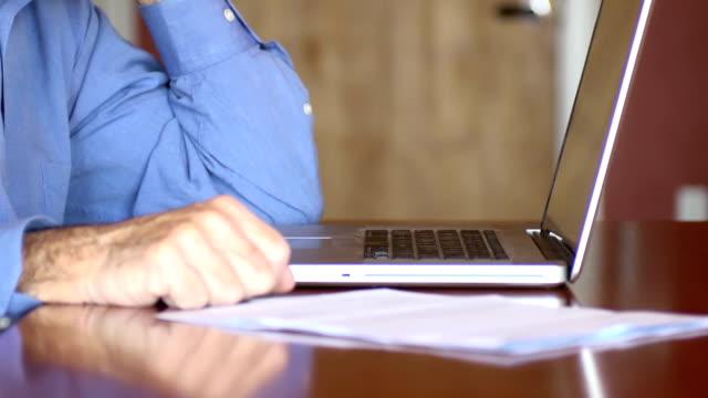 Senior Man Discusses Documents over Phone - CU video