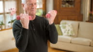 SLO MO senior man doing hand weights exercises at home video