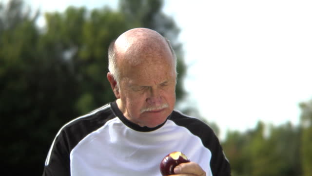 Senior man eating apple and drinking water video
